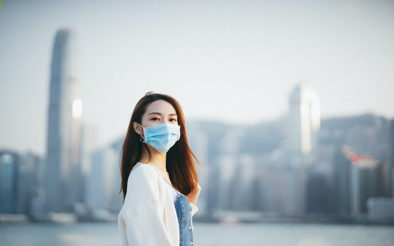Young Asian woman wearing a protective face mask to prevent the spread of coronavirus in the city, a global health emergency over outbreak