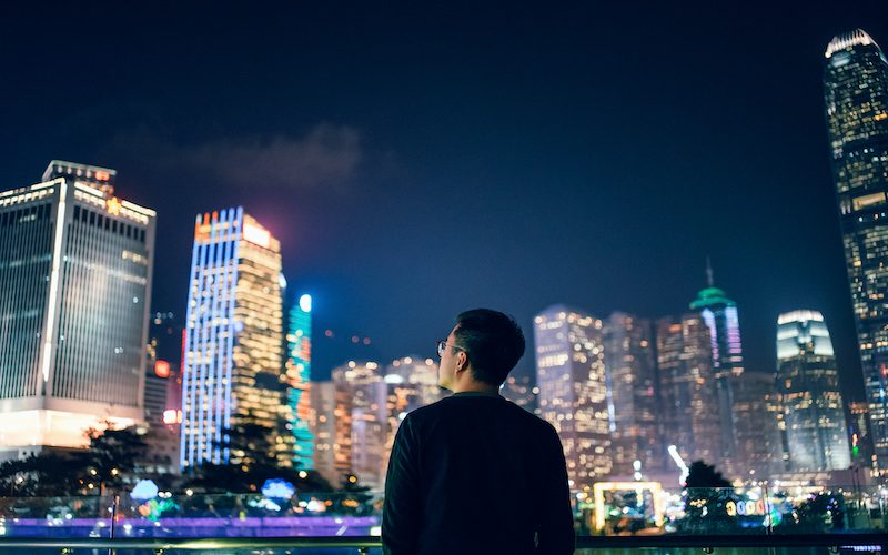 Rear view of young man looking towards the prosperity of Hong Kong city skyline in downtown financial district