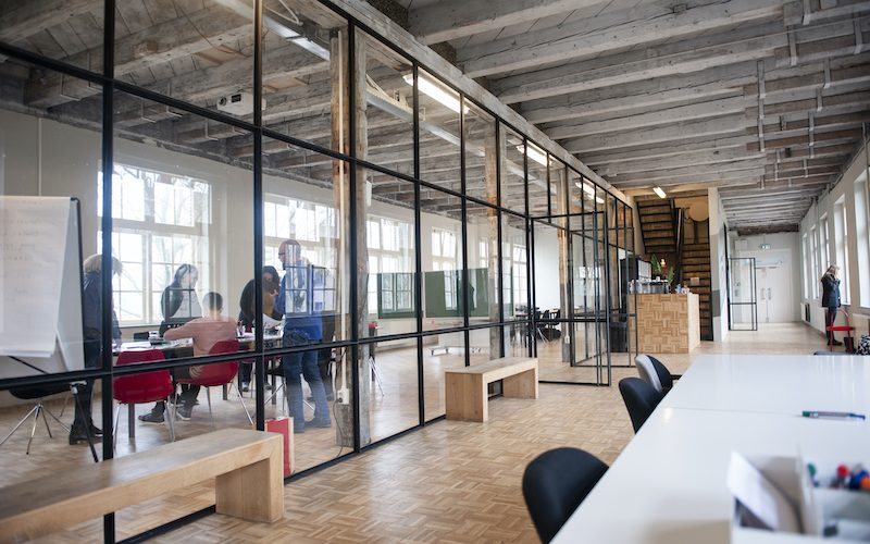 Beautiful modern office space in an old building. A team is working and a woman is making a phone call in the hallway