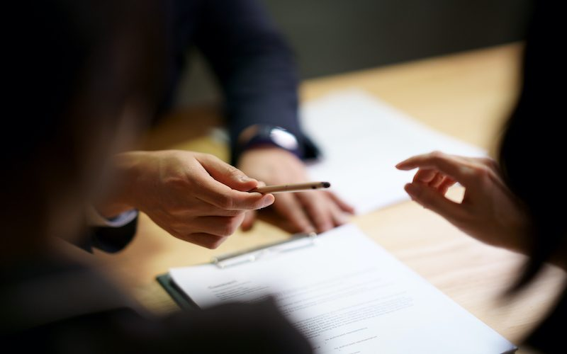 Selective focus shooting on hand of Businessman giving pen to Partnership to sign contract agreement in document  / Sign contract agreement in business (Selective focus shooting on hand of Businessman giving pen to Partnership to sign contract agreeme