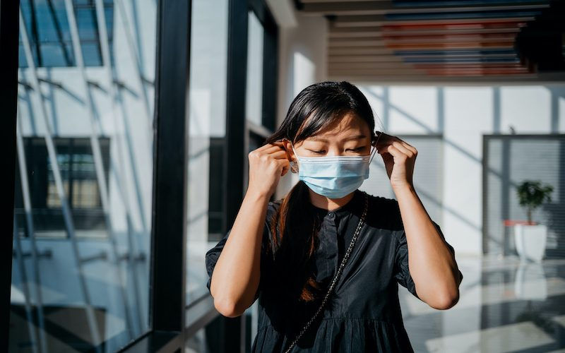 A shot of young Asian woman wearing protective face mask before heading out for work