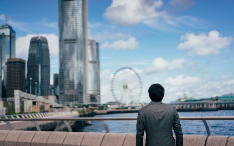 Rear view of young asian business handsome man looking at modern building. Portrait of asian businessman in outdoor with Hong Kong business district background (Rear view of young asian business handsome man looking at modern building. Portrait of asi