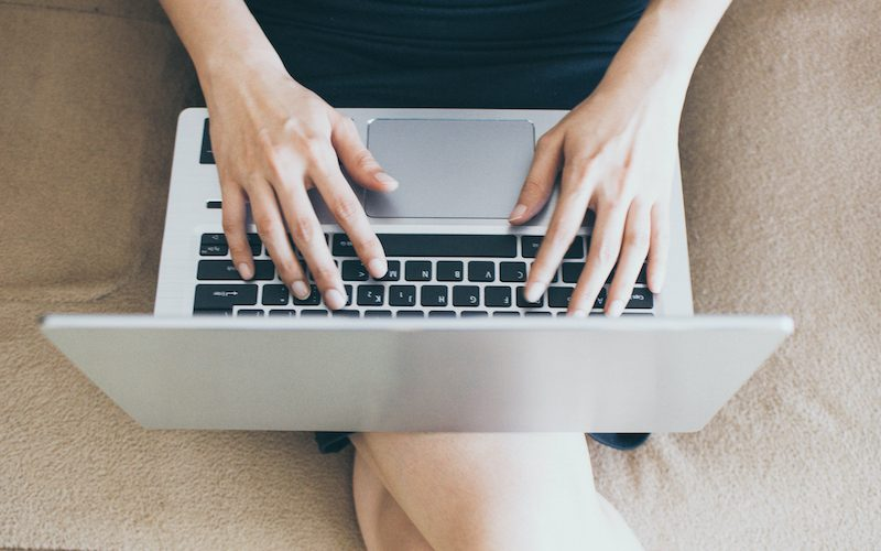 A young woman is working at home while sitting in the living room using internet connectivity