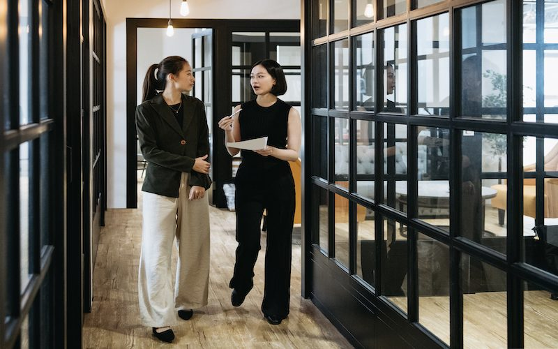 Two women wearing smart clothing discussing in hallway with docuement