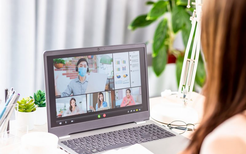 telework concept - Back view of asian woman use laptop to join a video meeting and her team member is self quarantine at home because coronavirus
