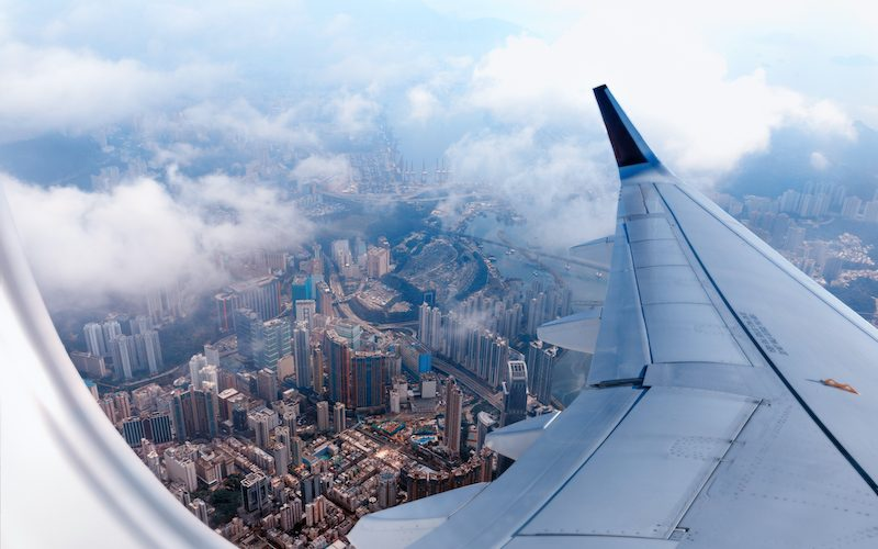 Plane to Hong Kong. Airplane window view at the skyscrapers. Overhead city view. Cityscape aerial. Concept of travel and air transportation.  (Plane to Hong Kong. Airplane window view at the skyscrapers. Overhead city view. Cityscape aerial. Concept o
