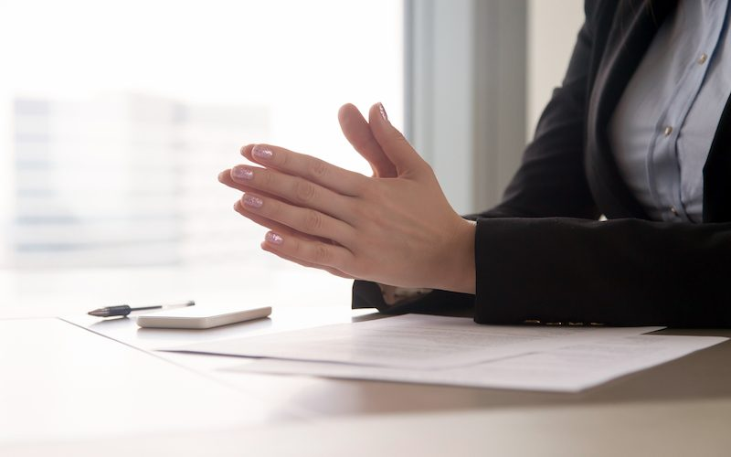 Close up view of female hands put together as in prayer in the office. Focused concentrated job applicant is nervous waiting for interview, businesswoman collecting thoughts before important meeting