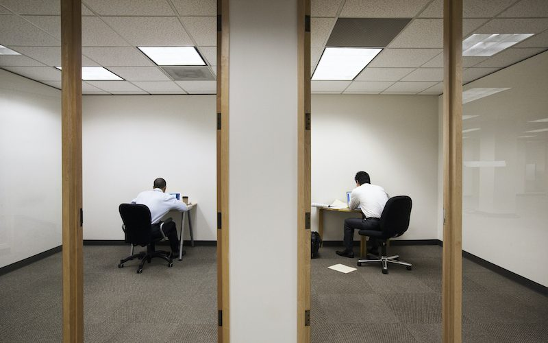 A view of two businessmen working on opposite sides of a wall in two different office spaces.