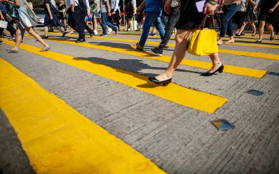 Unrecognizable crowd crossing pedestrian crosswalk, low angle view in Hong Kong