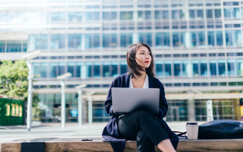 Medium shot of a motivated young Asian businesswoman working with laptop, sitting on the bench, against modern corporate buildings in the city, in daytime.