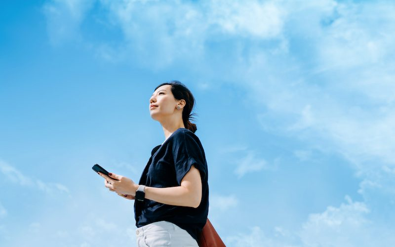 Low angle portrait of confident young Asian businesswoman using smartphone, looking up to sky with positive mind, standing against blue sky in the city. Female leadership and determined to success