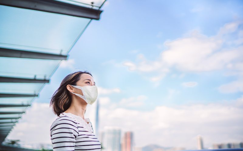Young Asian woman wearing a face mask to protect and prevent from the spread of viruses in the city.