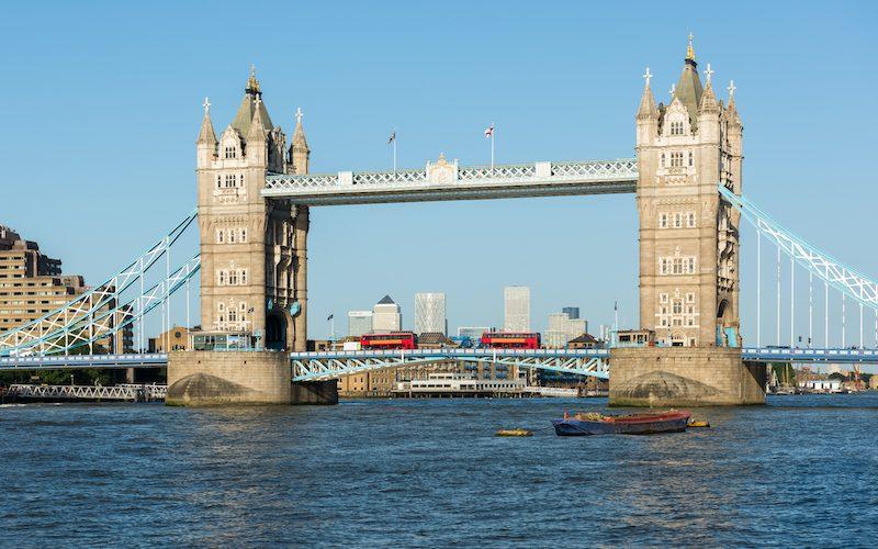 Two red double decker London buses crossing Tower Bridge, London.