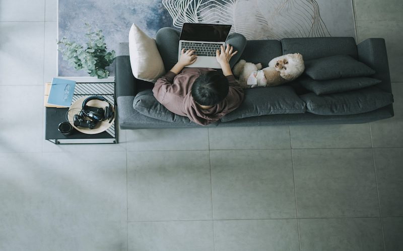 an asian chinese mid adult woman working from home with her laptop on sofa with her pet toy poodle