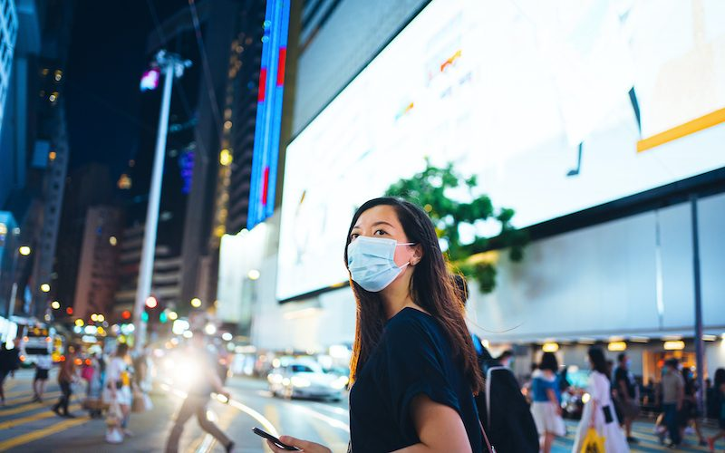 Young Asian woman with protective face mask using smartphone while commuting in downtown city street admist crowd of pedestrians and city buildings with illuminated and multi-coloured commercial signs at night