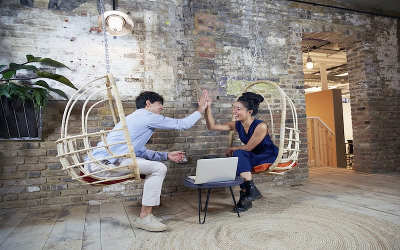 two young people doing high five at work