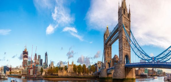 Panoramic London skyline with iconic symbol, the Tower Bridge and Her Majesty's Royal Palace and Fortress, known as the Tower of London as viewed from South Bank of the River Thames in the morning light