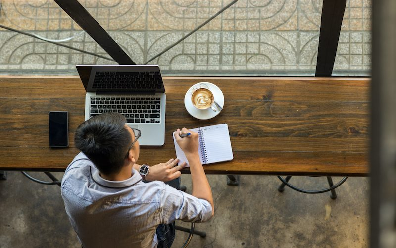 Young Asian businessman taking note beside laptop on wooden table