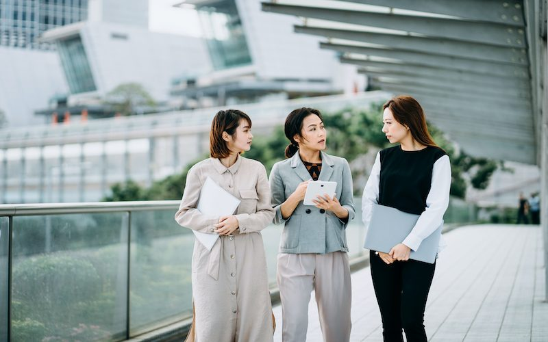 A group of businesswomen holding paperworks and using digital tablet walking together and discussing on a business project outdoors against city scene in front of modern office buildings