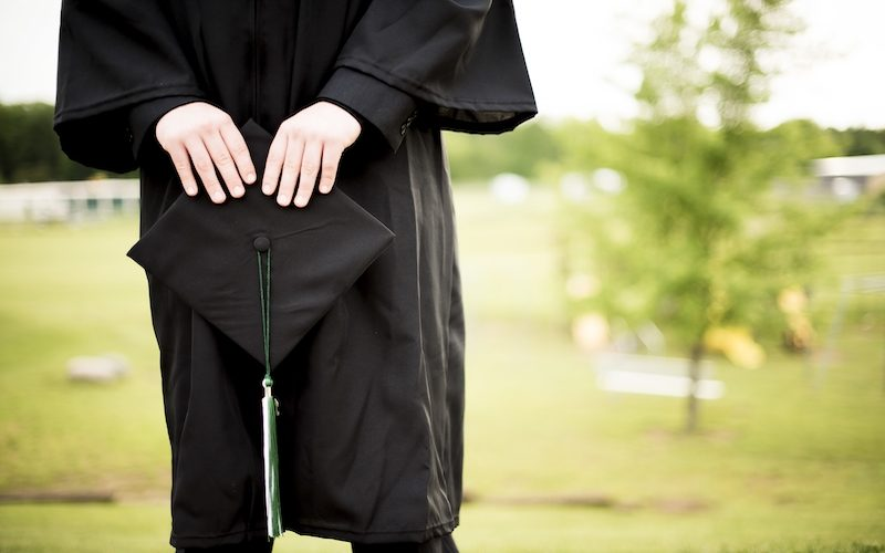 A shallow focus shot of a graduate holding its hat with a blurred background