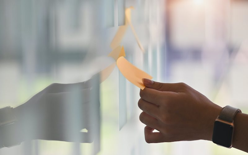 Side shot hands of young business man while sticky post it on glass. Meeting and sharing idea concept. Reminder schedule board. (Side shot hands of young business man while sticky post it on glass. Meeting and sharing idea concept. Reminder schedule b