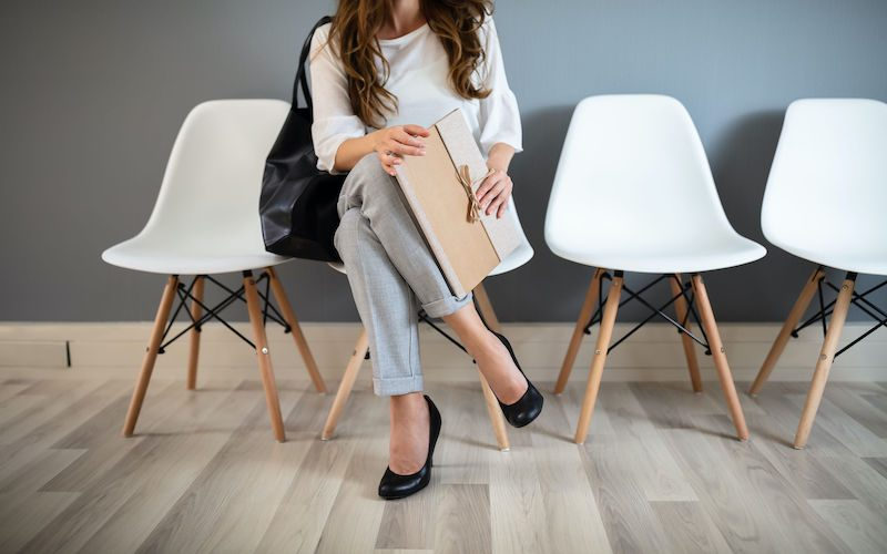 Young Businesswoman Holding Folder While Sitting On Chair Waiting For Job Interview