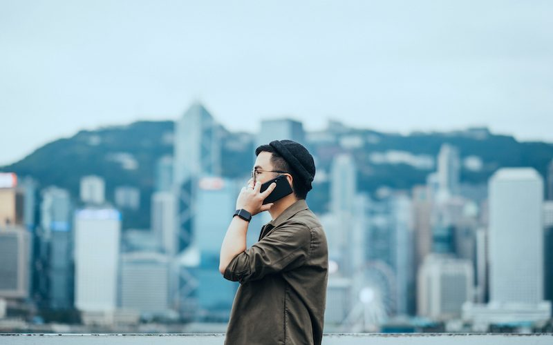 Stylish young Asian man talking on the phone outdoors against contemporary city skyline