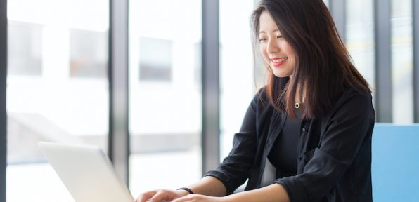 A portrait of an Asian college or university student at campus. She is sitting at the table with a laptop studying next to the windows